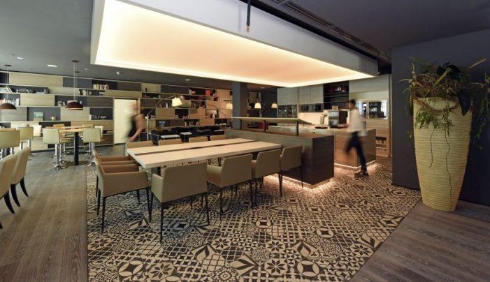 ...lange Arbeits- und Meeting-Tafeln, die offene Küche und natürlich Workstations mit jeder Menge Anschlüsse und Steckdosen.