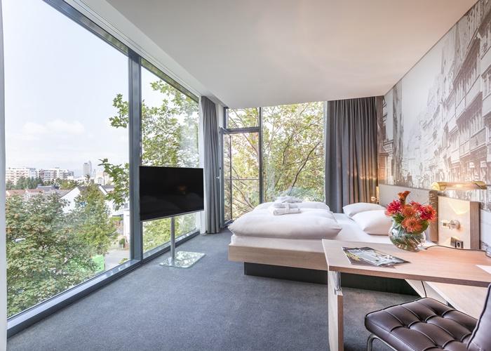 SchönerWohnen & Arbeiten: Serviced Apartment im neuen Haus in Frankfurt mit Living-Area, Working-Station, voll ausgestatteter Küche und Blick auf die Skyline der Stadt.
