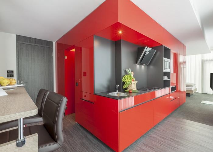 Allin One: hinter der roten Lackfront verbirgt sich der Eingang zum Bad (links), die Küche samt Induktionsherd, Kühlschrank und Mikrowelle und der großzügige Schrank.